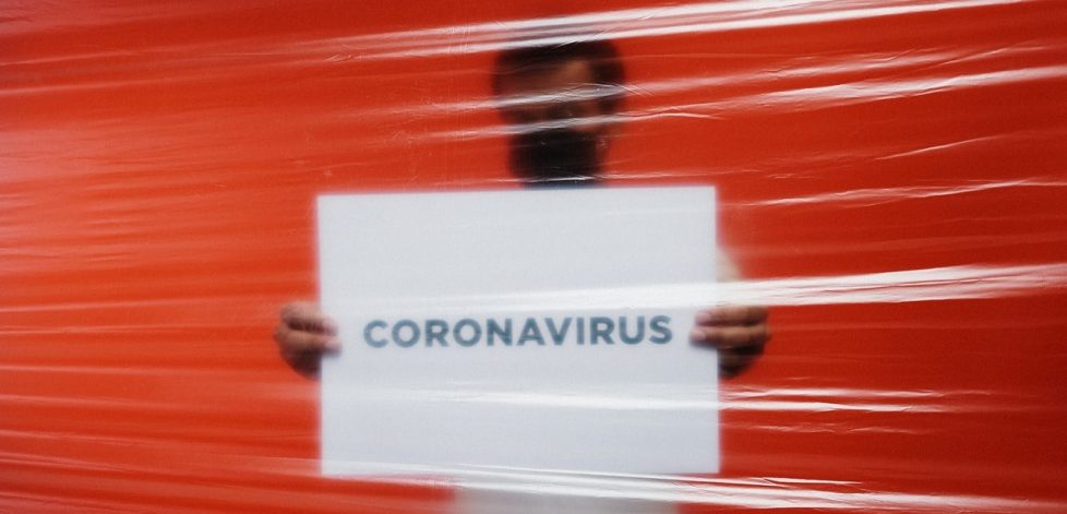 man-behind-a-plastic-holding-a-poster-of-coronavirus-3952185